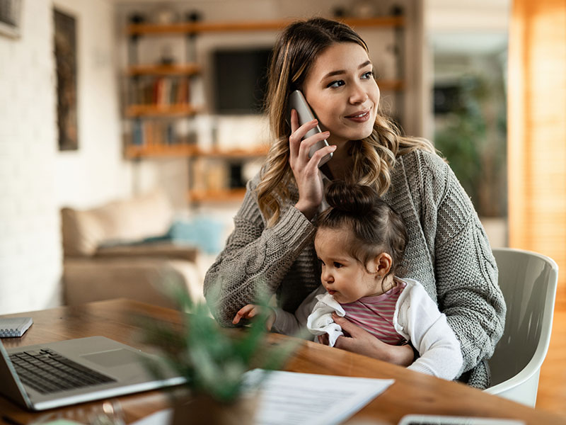 Woman talking on phone while holding baby