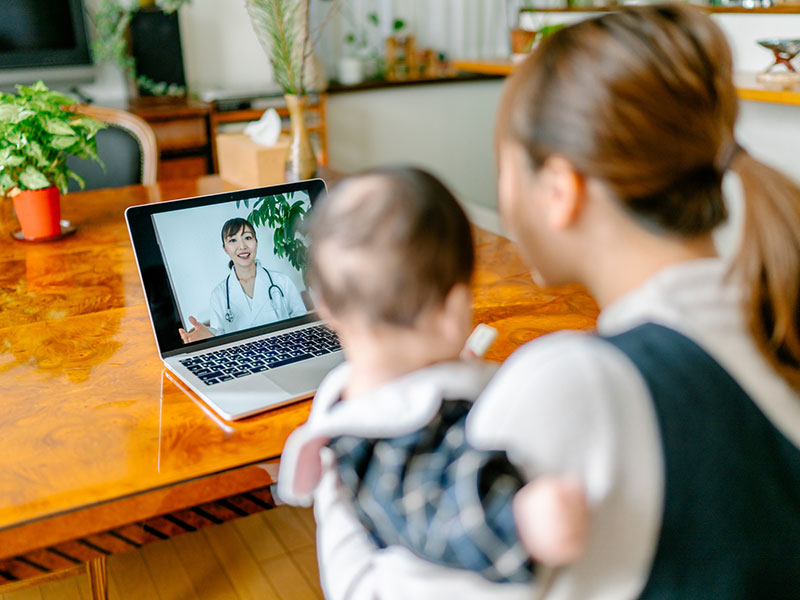 Woman holding baby while on video call with doctor